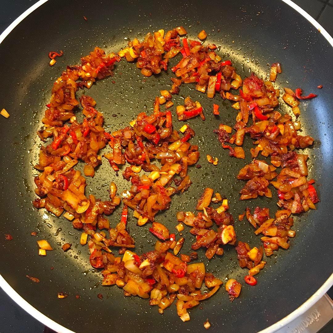 Tillsätt muscovadosocker, rökt paprikapulver och tomatpuré och stek på i ytterligare några minuter under omrörning.