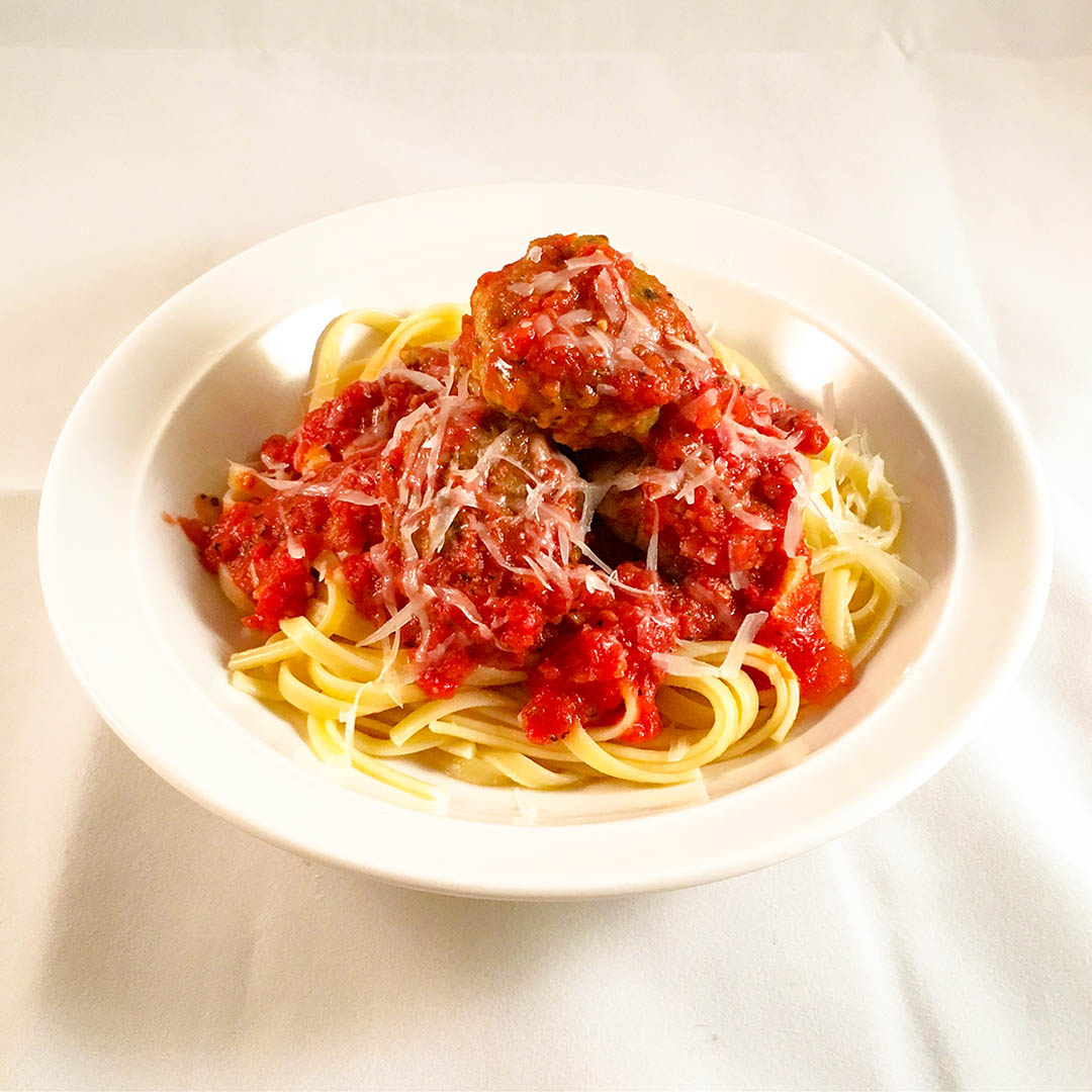 Kycklingköttbullar fylld med pesto i tomatsås.