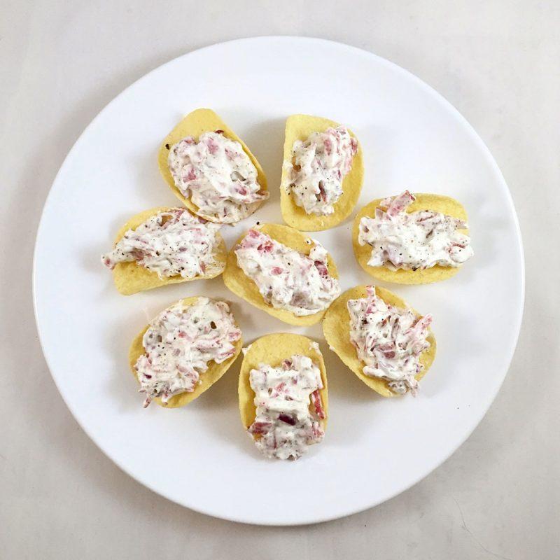 Potatischips med crème på pepparsalami och rödlök.