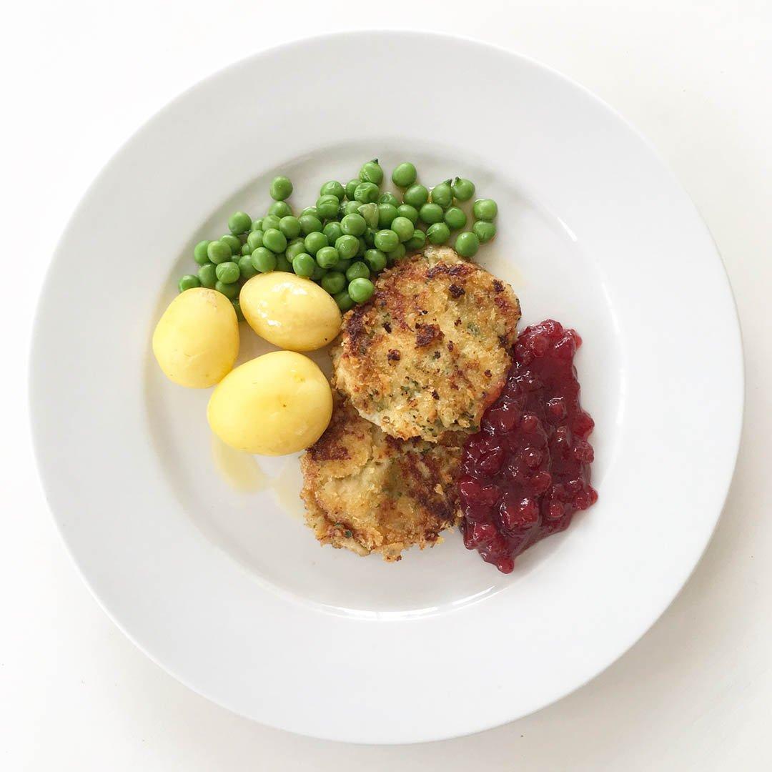 Gäddfärsbiffar med skirat smör, gröna ärtor, potatis och lingonsylt.