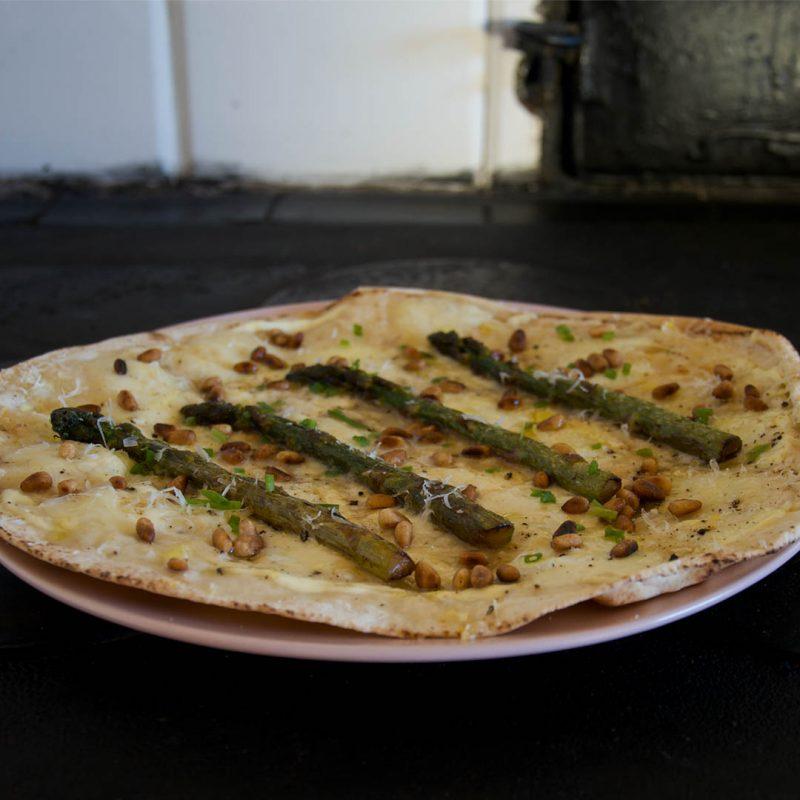 Libapizza Bianca med crème fraiche, sparris och pinjenötter. Men parmesan, mozzarella, citronzest, gräslök och lite honung ska du även ha på.